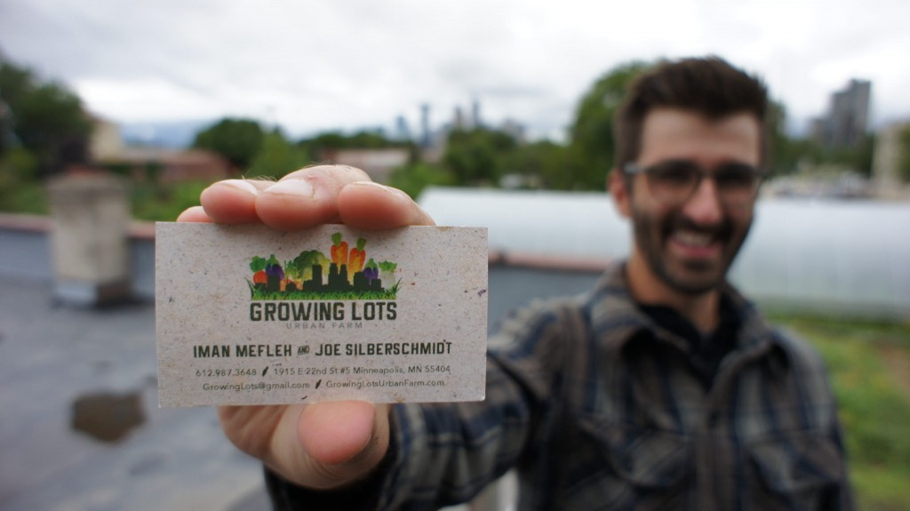 Owner of Growing Lots urban Farms holding business card outdoors.